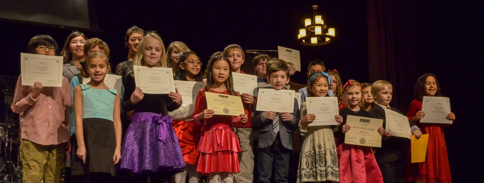Twenty plus The Art of Piano students line up with their certificates after the 2014 Winter recital